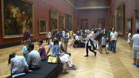 Vele mensen waarderen schilderijen en standbeelden in het Louvremuseum in Parijs, Frankrijk stock footage