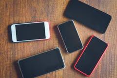 Vele mobiele telefoons op de houten lijst stock afbeeldingen