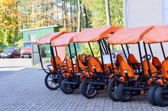 Vele modieuze oranje vierwielige sportenfietsen, cycluskaarten voor de recreatie en het toerisme van familiesporten met een wiel  stock fotografie