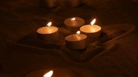 Vele mooie, ronde, kleine witte kaarsen die in het zand in dark branden stock video