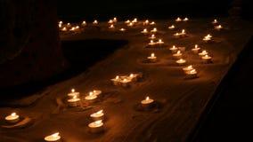 Vele mooie, ronde, kleine witte kaarsen die in het zand in dark branden stock videobeelden