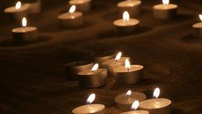 Vele mooie, ronde, kleine witte kaarsen die in het zand in dark branden stock footage