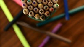 Vele multicolored potloden bewegen zich in een cirkel op een zwarte houten achtergrond met tellers Conceptenbureau of school, ken stock videobeelden