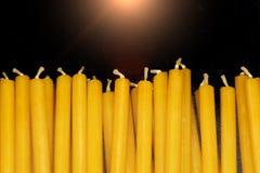 Vele natuurlijke dunne gele kaarsen liggen op zwarte achtergrond royalty-vrije stock foto's