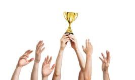 Vele omhoog opgeheven handen De winnaar houdt trofee in handen Geïsoleerdj op witte achtergrond Stock Foto