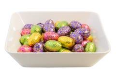 Vele paaseieren in kleurrijk verpakkingsmateriaal in een kom Royalty-vrije Stock Foto's