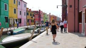 Vele passers mensen lopen voorbij kleurrijke huizen langs dorpsstraat met van de waterkanaal en motor boten stock videobeelden