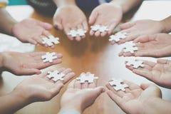 Vele personen die stukken van puzzel, Groepswerkconcept, zakenrelatie, Succes en strategieconcept, Bedrijfsaccountin houden royalty-vrije stock foto's