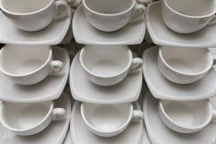 Vele rijen maken witte koffiekop, theelepel en schotel op lijst schoon De lege die mok in rij wordt geplaatst treft voor koffiepa Royalty-vrije Stock Foto's