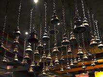 Vele rituele klokken die op kettingen van het plafond hangen Stock Foto's