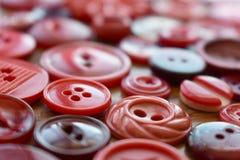 Vele rode naaiende knopen op een houten lijst Stock Fotografie