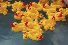Vele rubber gele stuk speelgoed eenden die in kinderen` s pool drijven stock foto