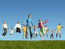 Vele springende families op het gras, collage stock afbeeldingen