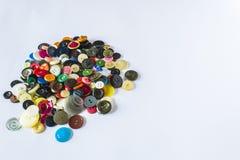 Vele verschillende knopen Knopen voor kleren van plastiek worden gemaakt dat De knopen zijn verspreid op een lichte achtergrond V Stock Foto's