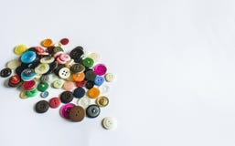 Vele verschillende knopen Knopen voor kleren van plastiek worden gemaakt dat De knopen zijn verspreid op een lichte achtergrond V Stock Afbeeldingen