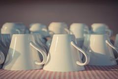 Vele witte koffiekoppen in een lijn teisteren voor ontbijt Stock Afbeelding