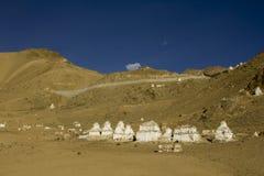 Vele witte Tibetaanse Boeddhistische stupas van tempels op de helling van een woestijnberg tegen een schone blauwe hemel royalty-vrije stock afbeeldingen