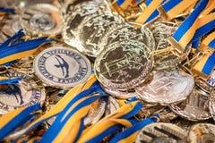Vele zilveren medailles met blauwe linten op een zilveren dienblad, toekenning van kampioenen, sportverwezenlijkingen, tweede pla Stock Foto