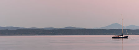 Veleiro ancorado em um lago com as montanhas no fundo no por do sol imagens de stock
