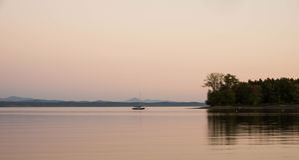 Veleiro ancorado em um lago com as montanhas no fundo no por do sol foto de stock royalty free