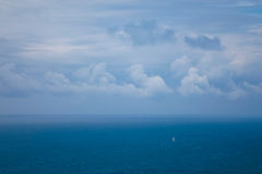 Veleiro pequeno no oceano sob um céu nebuloso Foto de Stock Royalty Free
