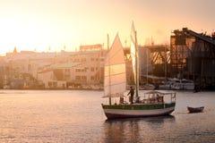 Veleiro que entra o porto perto de Granville Island, Vancôver, com o ajuste do sol no fundo fotografia de stock royalty free