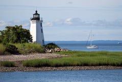 Veleiro que passa pelo farol preto do porto da rocha em Connecticut Fotos de Stock