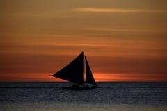 Veleiro só no fundo do por do sol sobre o mar na ilha de Boracay, Filipinas fotografia de stock