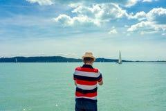 Veleiros de observação do homem da costa no lago Hungria Balaton foto de stock royalty free