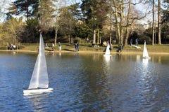 Veleiros modelo em uma lagoa em um parque em Paris Os pássaros voam, pais andam com crianças, gansos em uma lagoa fotografia de stock