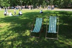 Velen die stoelen in Hyde Park in de stad Londen vouwen Stock Afbeeldingen