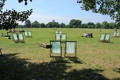 Velen die stoelen in Hyde Park in de stad Londen vouwen Stock Afbeelding