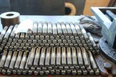 Velen glanzend metaal beslaan met gravure, noten, ijzerringen, pakkingen, metaalbewerkingshulpmiddelen en industriële bankschroef stock afbeelding