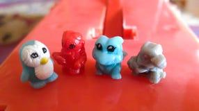 Velen kleine poppen dierlijke plaats op de rode plastic basis stock fotografie