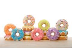 Velen kleurrijk die suikergoed donuts op een lichte houten geïsoleerde lijst met een laag wordt bedekt stock afbeeldingen