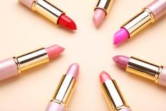 Velen kleurrijke lippenstift op beige vlakke achtergrond, leggen royalty-vrije stock foto