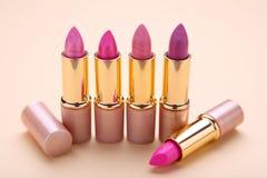 Velen kleurrijke lippenstift op beige vlakke achtergrond, leggen stock foto