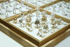 Velen typen gemring jewely schikken op de gouden plaat in de opslag van de doosjewely van de vertoningsspiegel stock foto's