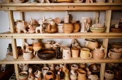 Velen verschillend aardewerk dat zich op de planken in een aardewerkworkshop bevindt Laag licht Royalty-vrije Stock Foto