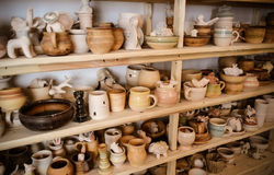Velen verschillend aardewerk dat zich op de planken in een aardewerkworkshop bevindt Laag licht Stock Fotografie