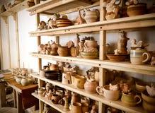 Velen verschillend aardewerk dat zich op de planken in een aardewerkworkshop bevindt Laag licht Stock Afbeeldingen