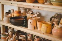 Velen verschillend aardewerk dat zich op de planken in een aardewerkworkshop bevindt Laag licht Stock Foto