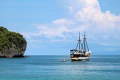 Velero blanco en el océano con las vistas de la isla y del azul fotos de archivo libres de regalías
