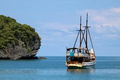 Velero blanco en el océano con las vistas de la isla y del azul fotografía de archivo