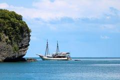 Velero blanco en el océano con las vistas de la isla y del azul imagen de archivo