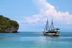 Velero blanco en el océano con las vistas de la isla y del azul imagen de archivo libre de regalías