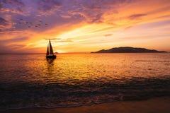 Velero en el océano en la salida del sol Fotos de archivo libres de regalías