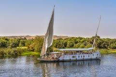 Velero en el río el Nilo cerca de la orilla verde, turistas que se sientan en la cubierta fotos de archivo libres de regalías