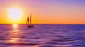 Velero en la puesta del sol Foto de archivo libre de regalías
