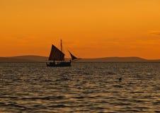 Velero en la puesta del sol Fotos de archivo libres de regalías